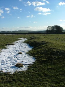 The earthwork bank and ditch close to the henge.The snow highlights the ditch which is on the outside and appears to create an area surrounding the henge.